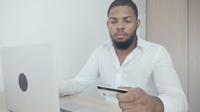Αφρικανικός νεαρός άνδρας που ψωνίζει on-line με την πιστωτική κάρτα που χρησιμοποιεί το lap-top στο σπίτι απόθεμα βίντεο