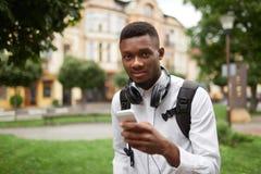Αφρικανικός σπουδαστής που κουβεντιάζει, μήνυμα γραψίματος με το έξυπνο τηλέφωνο Στοκ εικόνα με δικαίωμα ελεύθερης χρήσης