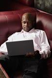 Αφρικανικός τύπος με το lap-top στον καναπέ Στοκ Φωτογραφία