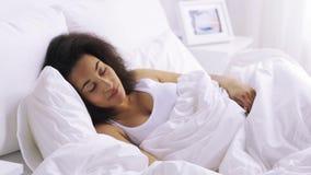 Αφρικανικός ύπνος γυναικών στην κρεβατοκάμαρα κρεβατιών στο σπίτι απόθεμα βίντεο