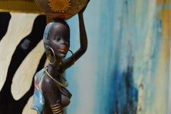 Αφρικανικό άγαλμα ενός κοριτσιού με ένα δοχείο στο κεφάλι του με μια εθνική καταγωγή πίσω Στοκ Φωτογραφία