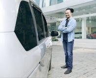 Αφρικανικό άτομο με το νέο αυτοκίνητό του στην αίθουσα εκθέσεως Στοκ εικόνες με δικαίωμα ελεύθερης χρήσης