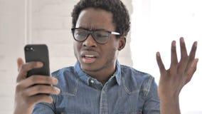 Αφρικανικό άτομο που αντιδρά στην απώλεια σε Smartphone απόθεμα βίντεο