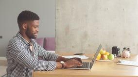 Αφρικανικό άτομο στη συνεδρίαση περιστασιακής ένδυσης στον πίνακα μπροστά από το ανοικτό lap-top στο σπίτι απόθεμα βίντεο