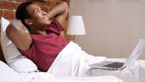 Αφρικανικό άτομο στο κρεβάτι που λειτουργεί στο lap-top και που αντιδρά στην επιτυχία απόθεμα βίντεο