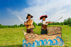 Αφρικανικό αγόρι, κορίτσι στα κοστούμια πειρατών με τα ξίφη Στοκ Φωτογραφίες