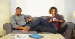Αφρικανικό ζεύγος που χρησιμοποιεί τις ηλεκτρονικές συσκευές στον καναπέ Στοκ φωτογραφία με δικαίωμα ελεύθερης χρήσης