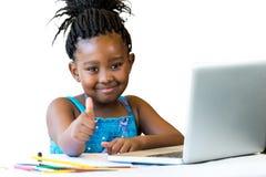 Αφρικανικό παιδί που κάνει τους αντίχειρες επάνω στο γραφείο που απομονώνεται Στοκ Φωτογραφίες