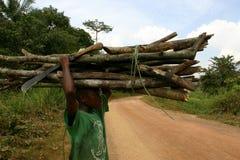 Αφρικανικό φέρνοντας καυσόξυλο αγοριών και ένα μεγάλο μαχαίρι στοκ φωτογραφία