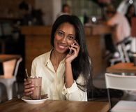 Αφρικανικό χαμόγελο γυναικών που μιλά στην έξυπνη τηλεφωνική χαλάρωσή της στον τοπικό καφέ που απολαμβάνει τον καφέ πρωινού της Στοκ εικόνες με δικαίωμα ελεύθερης χρήσης
