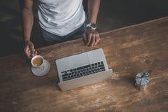 Αφροαμερικάνος με τον καφέ και το lap-top Στοκ Εικόνα
