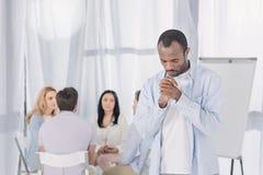 αφροαμερικάνος που προσεύχεται ενώ άνθρωποι που κάθονται πίσω κατά τη διάρκεια στοκ φωτογραφία με δικαίωμα ελεύθερης χρήσης