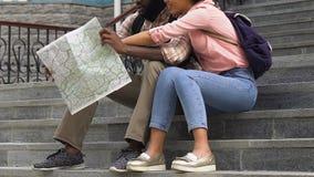 Αφροαμερικανίδα συνεδρίαση ζευγών στα σκαλοπάτια, που εξετάζουν το χάρτη για να βρεί το διάσημο ορόσημο απόθεμα βίντεο