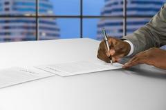 Αφροαμερικανικός υπογράφει το έγγραφο στο γραφείο Στοκ Εικόνα