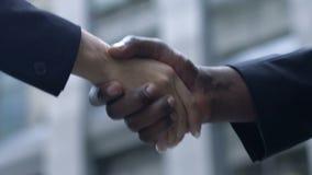 Αφροαμερικανός άνδρας και καυκάσια χέρια τινάγματος γυναικών, διεθνής συνεργασία απόθεμα βίντεο