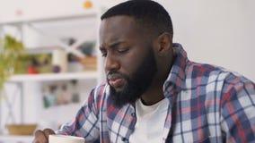 Αφροαμερικανός άτομο που πίνει το καυτό ποτό και που αισθάνεται τον πονόδοντο, ευαίσθητο σμάλτο απόθεμα βίντεο