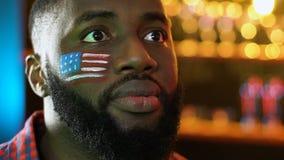 Αφροαμερικανός αθλητικός ανεμιστήρας με την αμερικανική σημαία που ανατρέπεται για το αγαπημένο χάνοντας παιχνίδι ομάδων απόθεμα βίντεο