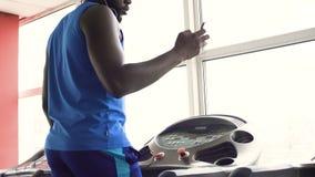 Αφροαμερικανός αρσενικό περπάτημα treadmill και μεταφόρτωση της ικανότητας app στο κινητό τηλέφωνο απόθεμα βίντεο