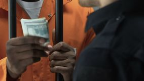Αφροαμερικανός εγκληματίας που δίνει τα χρήματα ως δωροδοκία στο δεσμοφύλακα, που παραβαίνει το νόμο φιλμ μικρού μήκους