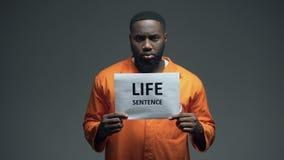 Αφροαμερικανός φυλακισμένο αρσενικό σημάδι ισόβια εκμετάλλευσης, που κοιτάζει στη κάμερα φιλμ μικρού μήκους