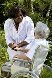 Αφροαμερικανός caregiver που φροντίζει μια με ειδικές ανάγκες ανώτερη γυναίκα στοκ εικόνες