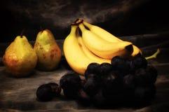 Αχλάδια και μπανάνες σταφυλιών στο γκρίζο σκηνικό στούντιο στοκ φωτογραφίες με δικαίωμα ελεύθερης χρήσης