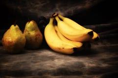 Αχλάδια και μπανάνες στο γκρίζο σκηνικό στούντιο στοκ φωτογραφία