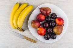 Αχλάδια, νεκταρίνια και δαμάσκηνα στο πιάτο, δέσμη των μπανανών, μαχαίρι Στοκ εικόνες με δικαίωμα ελεύθερης χρήσης
