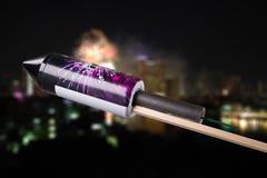 Αχρησιμοποίητος πύραυλος πυροτεχνουργίας μπροστά από μια μουτζουρωμένη πόλη με το firewo στοκ εικόνες