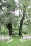 Αψίδα λουλουδιών για το γάμο και άσπρες καρέκλες στο πράσινο πάρκο στοκ εικόνες