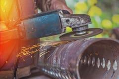 Αλέθοντας σωλήνας χάλυβα εργαζομένων με το μύλο Στοκ Φωτογραφίες