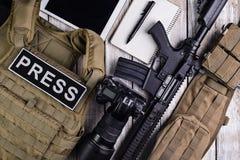 Αλεξίσφαιρες φανέλλα, κάμερα, τουφέκι, σημειωματάριο, ζώνη στρατού και ταμπλέτα touc Στοκ Φωτογραφίες