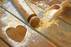 Αλεύρι, κυλώντας καρφίτσα και καρδιά με το ξύλινο υπόβαθρο Στοκ εικόνα με δικαίωμα ελεύθερης χρήσης