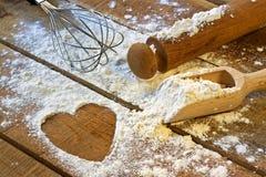 Αλεύρι, κυλώντας καρφίτσα και καρδιά με το ξύλινο υπόβαθρο Στοκ Εικόνα