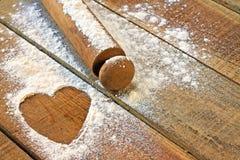 Αλεύρι, κυλώντας καρφίτσα και καρδιά με το ξύλινο υπόβαθρο Στοκ Εικόνες