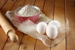 Αλεύρι στο κύπελλο με τα αυγά και κυλώντας καρφίτσα πέρα από τον ξύλινο πίνακα Στοκ εικόνα με δικαίωμα ελεύθερης χρήσης