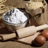 Αλεύρι στο κύπελλο, τα αυγά, το ρύζι και την κυλώντας καρφίτσα Στοκ Εικόνες