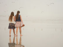 Αδελφές που απολαμβάνουν το χρόνο μαζί στην ομιχλώδη παραλία Στοκ Φωτογραφία
