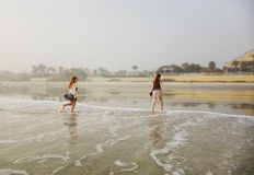 Αδελφές που απολαμβάνουν το χρόνο στην όμορφη ομιχλώδη παραλία στοκ εικόνα με δικαίωμα ελεύθερης χρήσης