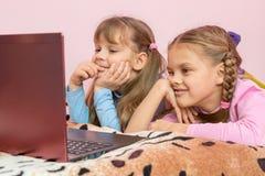 Αδελφές που βρίσκονται στο κρεβάτι που φαίνεται κινούμενα σχέδια lap-top Στοκ Εικόνες