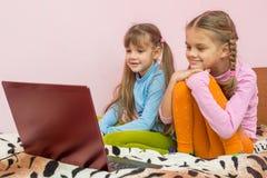 Αδελφές που εξετάζουν τα κινούμενα σχέδια lap-top Στοκ εικόνες με δικαίωμα ελεύθερης χρήσης