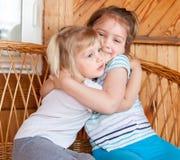 Αδελφές που κάθονται αγκαλιάζοντας ο ένας τον άλλον Στοκ φωτογραφία με δικαίωμα ελεύθερης χρήσης