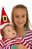 Αδελφές που φορούν τις πυτζάμες και αδελφή μωρών σε ένα καπέλο santa στοκ εικόνες
