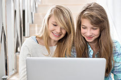Αδελφές που χρησιμοποιούν το lap-top στο κλιμακοστάσιο Στοκ εικόνα με δικαίωμα ελεύθερης χρήσης