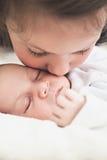 Αδελφή που φιλά το νεογέννητο αδελφό της Στοκ Φωτογραφίες