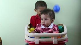 Αδελφοί που παίζουν με τις πολύχρωμες σφαίρες απόθεμα βίντεο