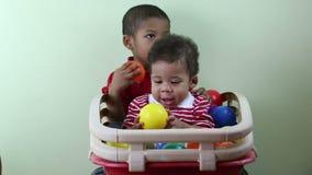 Αδελφοί που παίζουν με τις πολύχρωμες σφαίρες φιλμ μικρού μήκους