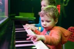 Αδελφοί που παίζουν στο ελαφρύ πιάνο μουσικής στοκ φωτογραφία