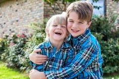 Αδελφοί στο ταίριασμα του γέλιου πουκάμισων καρό στοκ εικόνες