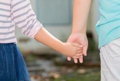 Αδελφός και αδελφές που κρατούν χέρι-χέρι Στοκ Φωτογραφία